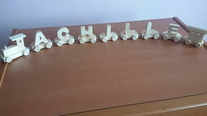Trenino in legno composto con il nome di Achille, ogni vagone è un carattere